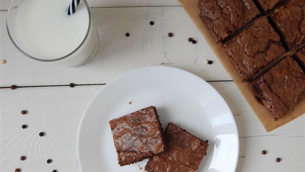 čokoládové brownies se sklenicí mléka na bílém dřevěném podkladu