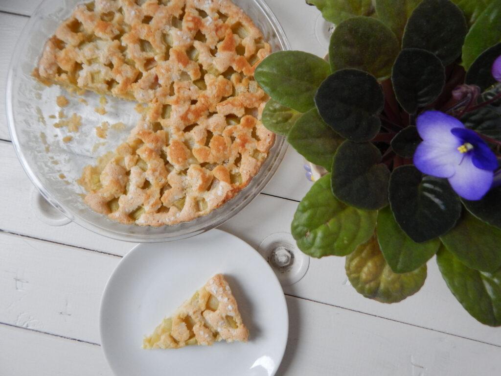 rebarborový koláč na dřevěném podkladu s fialkou v květináči